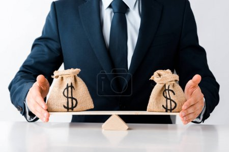 Photo for Cropped view of businessman touching scales with money bags isolated on white - Royalty Free Image