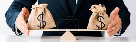 Photo for Panoramic shot of businessman touching scales with money bags isolated on white - Royalty Free Image