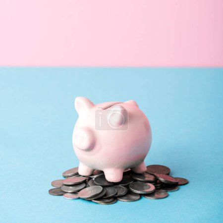 Photo pour Close up of coins near piggy bank isolated on blue and pink - image libre de droit