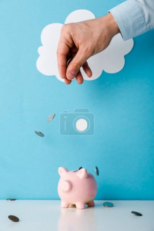 Photo pour Cropped view of man throwing coins near pink piggy bank on blue - image libre de droit
