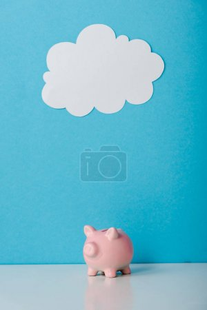 Photo pour Pink piggy bank near white cloud on blue with copy space - image libre de droit