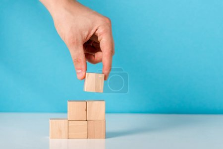 cropped view of man putting wooden cube on blue