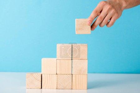 Photo pour Vue recadrée de l'homme d'affaires mettant cube en bois sur bleu - image libre de droit