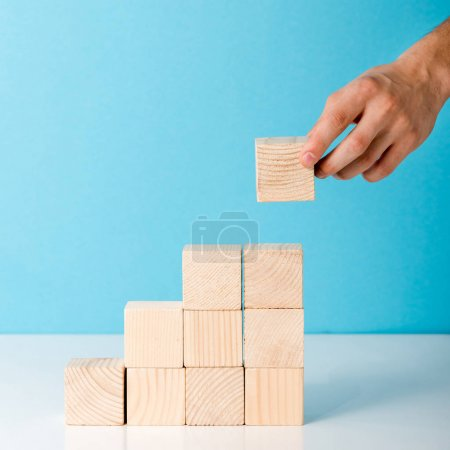 Photo for Cropped view of man putting wooden block on blue - Royalty Free Image