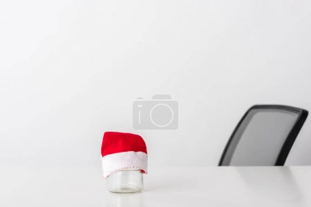 small santa hat on empty glass jar on white