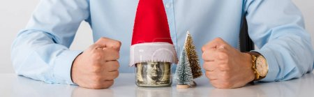 Photo pour Panoramic shot of man with clenched fists near glass jar with money and santa hat isolated on white - image libre de droit