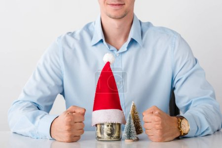 Foto de Cropped view of man with clenched fists near glass jar with money and santa hat isolated on white - Imagen libre de derechos