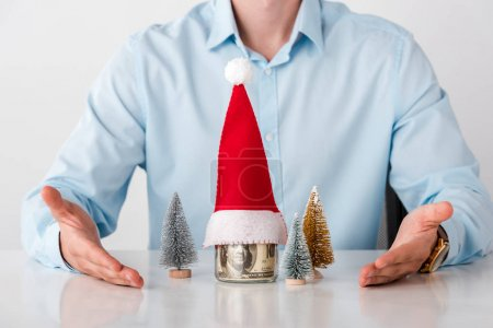 Photo pour Cropped view of man with pointing with hands at glass jar with money and santa hat isolated on white - image libre de droit