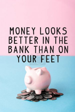 Photo for Silver coins near piggy bank and money looks better in the bank than on your feet letters on blue and pink - Royalty Free Image