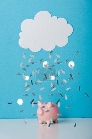Photo pour Tirelire rose près du nuage blanc et tombant pièces d'argent sur bleu - image libre de droit