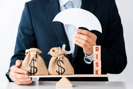 Photo for Cropped view of businessman holding carton umbrella near scales with money bags and wooden blocks with risk letters on white - Royalty Free Image