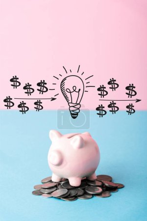 Photo pour Silver coins near piggy bank and light bulb on blue and pink - image libre de droit