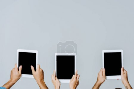 Photo for Cropped view of young friends holding digital tablets with blank screens isolated on grey - Royalty Free Image