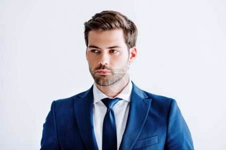 Photo pour Bel homme d'affaires en costume bleu à la recherche de suite isolé sur blanc - image libre de droit