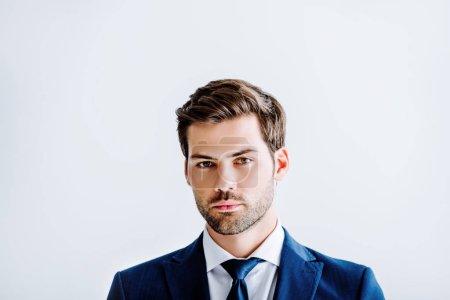 Photo pour Bel homme d'affaires en costume bleu regardant la caméra isolée sur blanc - image libre de droit