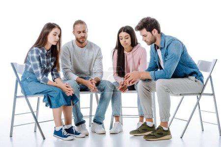 triste grupo de apoyo multicultural sentado en sillas aisladas en blanco