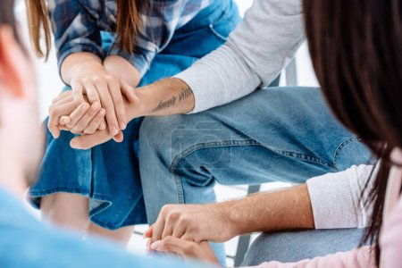 cropped view of support group holding hands while sitting on chairs isolated on white