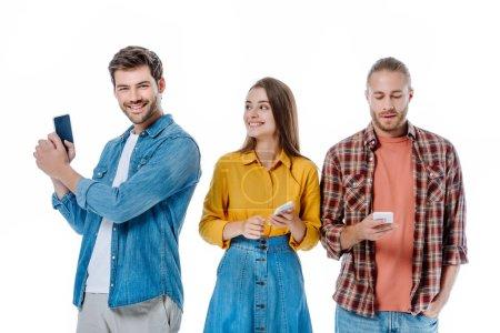 Photo pour Sourire trois jeunes amis tenant des smartphones isolés sur blanc - image libre de droit