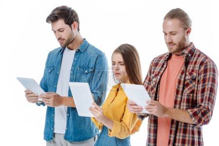 Photo pour Choqué trois jeunes amis utilisant des tablettes numériques isolées sur blanc - image libre de droit