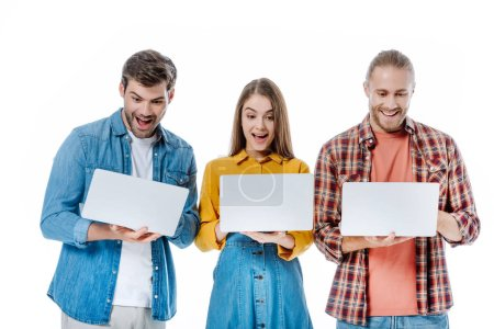 Photo for Happy young friends holding laptops with open mouths isolated on white - Royalty Free Image
