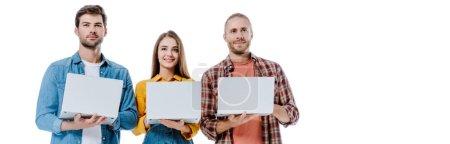 Photo pour Souriant trois jeunes amis tenant des ordinateurs portables isolés sur blanc, plan panoramique - image libre de droit