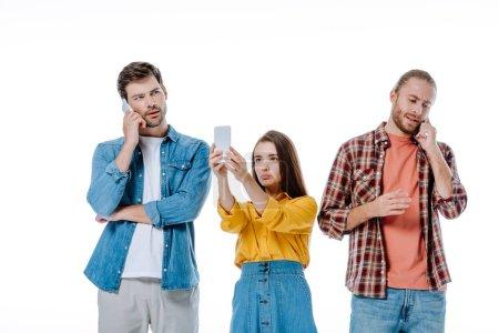 Photo pour Trois jeunes amis utilisant des smartphones isolés sur blanc - image libre de droit