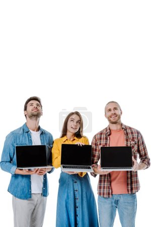 positive young friends holding laptops and looking up isolated on white
