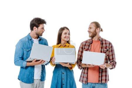 Photo pour Sourire trois jeunes amis tenant des ordinateurs portables isolés sur blanc - image libre de droit
