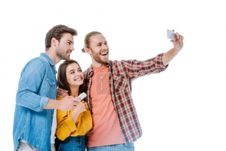 Photo for Smiling three young friends taking selfie on smartphone isolated on white - Royalty Free Image