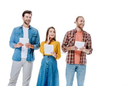 sourire trois jeunes amis tenant des tablettes numériques et regardant loin isolé sur blanc