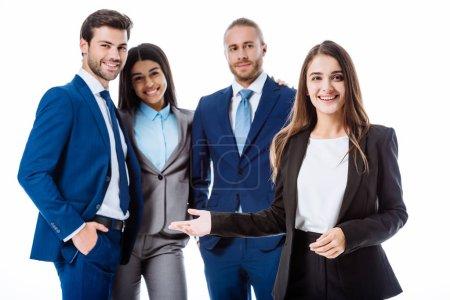 Photo pour Une femme d'affaires souriante montrant du doigt des gens d'affaires multiculturels en costume isolé sur blanc - image libre de droit