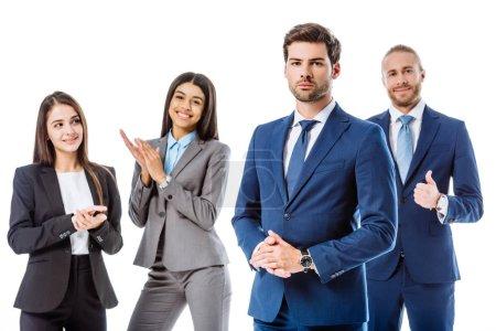 Photo pour Des gens d'affaires multiculturels souriants en costume applaudissant un homme d'affaires confiant - image libre de droit