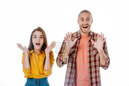 Photo pour Jeune couple en tenue décontractée avec bouche ouverte montrant les mains isolées sur blanc - image libre de droit