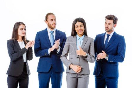 Photo pour Hommes d'affaires en costume applaudissant femme d'affaires africaine américaine souriante isolée sur blanc - image libre de droit