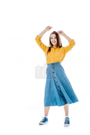 full length view of happy attractive girl dancing with hands in air and looking at camera isolated on white