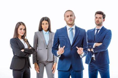 Photo pour Un homme d'affaires confiant montre un doigt moyen près de gens d'affaires multiculturels en costume isolé sur blanc - image libre de droit