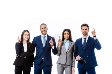 Photo for Multicultural business people in suits pointing with fingers up isolated on white - Royalty Free Image