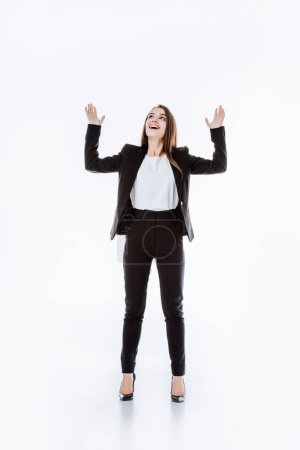 Photo for Happy businesswoman in suit with raised hands looking up isolated on white - Royalty Free Image