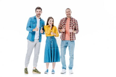 full length view of three happy young friends showing thumbs up isolated on white