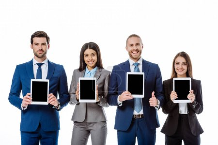 Photo for Smiling multicultural business people in suits showing digital tablets isolated on white - Royalty Free Image