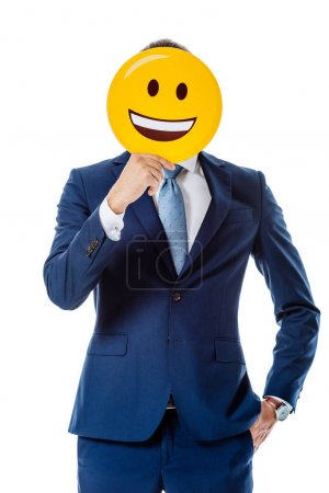 KYIV, UKRAINE - AUGUST 12, 2019: businessman in blue suit holding happy smiley in front of face isolated on white