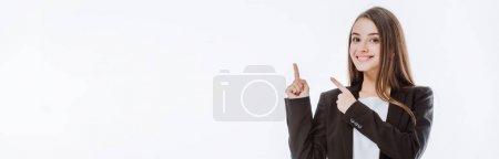 Photo pour Femme d'affaires souriante en costume pointant les doigts vers le haut isolé sur blanc, vue panoramique - image libre de droit