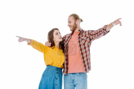Photo pour Jeune couple en tenue décontractée pointant les doigts loin et se regardant isolé sur blanc - image libre de droit