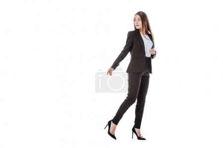 full length view of confident businesswoman in suit walking and looking away isolated on white