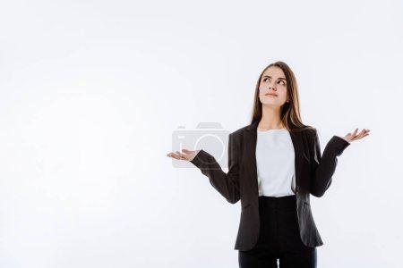 confusa mujer de negocios en traje mostrando gesto de encogimiento aislado en blanco