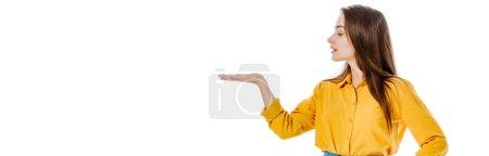chica atractiva señalando con la mano a un lado aislado en blanco, plano panorámico
