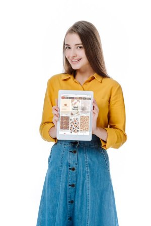 KYIV, UKRAINE - 12 AOÛT 2019 : fille souriante en jupe denim tenant tablette numérique avec application pinterest isolée sur blanc