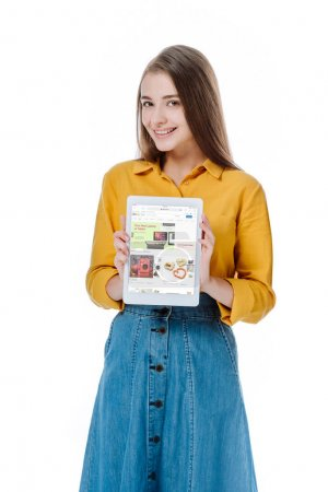 Photo for KYIV, UKRAINE - AUGUST 12, 2019: smiling girl in denim skirt holding digital tablet with ebay app isolated on white - Royalty Free Image