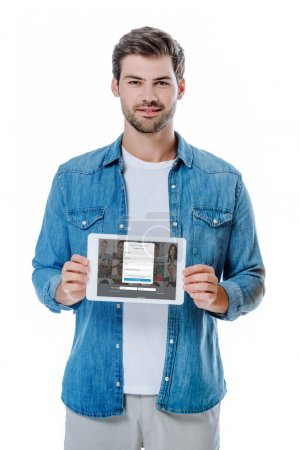 Photo pour KYIV, UKRAINE - AUGUST 12, 2019: smiling man in denim shirt holding digital tablet with linkedin page isolated on white - image libre de droit