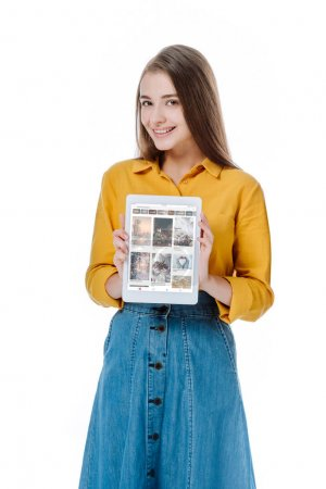 Photo for KYIV, UKRAINE - AUGUST 12, 2019: smiling girl in denim skirt holding digital tablet with pinterest app isolated on white - Royalty Free Image